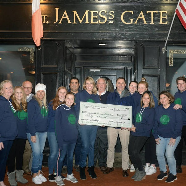 The Oysterfest volunteer team presents a check for $20,000 to the Melanoma Research Foundation